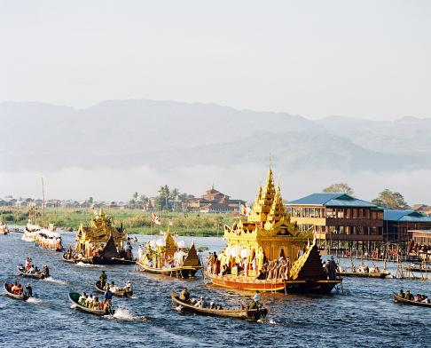 The Phaung Daw Oo Festival is held every October on Inle Lake. During the festival four gold figurines of Lord Buddha are transported clockwise around the lake over a period of several days, stopping off at various temples and monasteries along the way. There are a total of five golden Buddha statues, that all date from the 12th Century and throughout the year are housed at their 'resident' temple, The Phaung Daw Oo Pagoda, from which the festival draws its name. One of the five Buddha's always stays at the home temple during the procession - some say to guard the Pagoda, and others say because this particular Buddha has a bad omen associated with it, dating back to the 1965 procession. During that procession the Royal Barge whch transports the Buddha statues capsized and all of the figurines sank to the bottom. Only four were initially recovered, while the fifth one was feared lost, until it miraculously appeared back in the temple one day. The following year when the statue was loaded on to the barge a huge series of clouds appeared, so that was taken as a sign that that particular Buddha should remain and not join the procession. The Royal Barge is itself in the shape of the Royal Bird - picture a giant chicken - and is towed around the lake by dozens of smaller long-boats where Intha men practice their unique one-legged rowing style.
