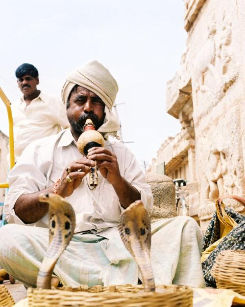 A snake charmer with his cobras outside the Virupaksha Temple in Hampi, Karnataka Province, India.