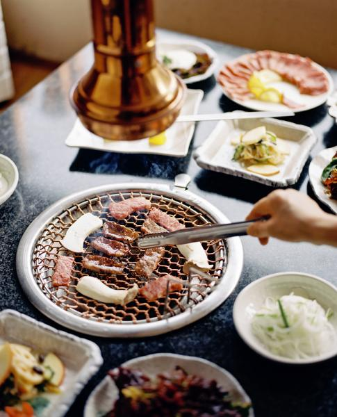 Park Daegamne BBQ Restaurant in Seoul, South Korea. Pictured here is meat on the barbecue grill along with several side dishes including: