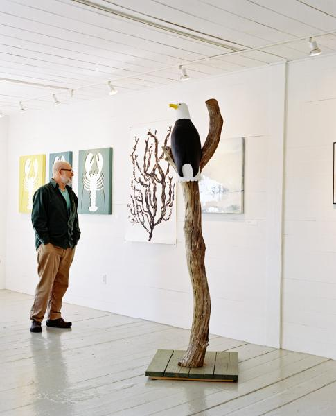 Artist David Wilson in front of some of his work at the Hopkins Wharf Gallery, by the ferry terminal on North Haven Island, Maine.