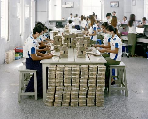 KBZ bank employees count kyat currency notes at one of the branches in Yangon, Myanmar. The country is a predominantly cash-based society and people purchase cars and homes with cash. The largest bill denomination is equivalent to ~ USD5, however those bills are rare and 1000 kyat (~USD1) are the most common.