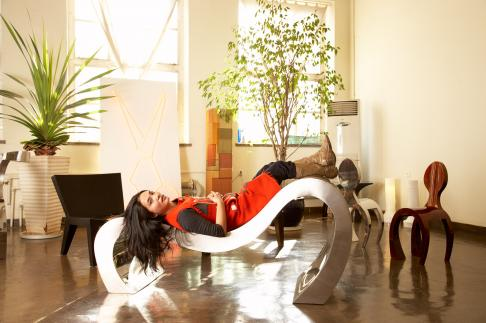 Lin Jing at her studio in the 798 Art complex in Beijing, also known as Dashanzi. Lin Jing is reclining on a piece called 'Long Island' made of aluminum.