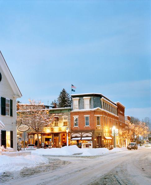 The center of Woodstock Vermont as dusk falls on a snowy winter's evening. Pictured in the photo in addition to the snow-covered streets is Bentley's restaurant.