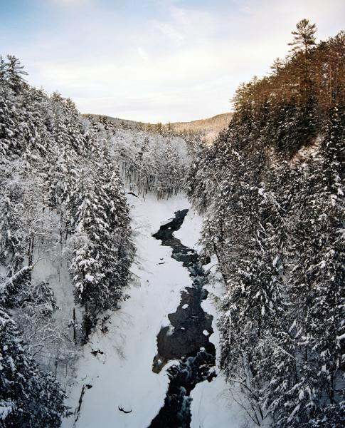 A winter scene just before dusk falls at Quechee Gorge on the Ottauquechee River, in Quechee Vermont. Quechee is located close to Woodstock, Vermont.