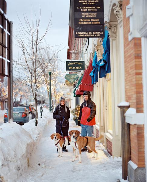 A couple out walking two dogs stops for a portrait on the snow-covered sidewalks of the main drag in Woodstock, Vermont.